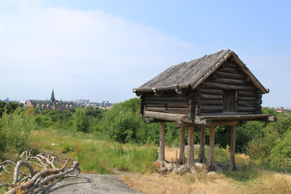Old dwelling at Skansen, featuring the Nordic Museum far in the background.